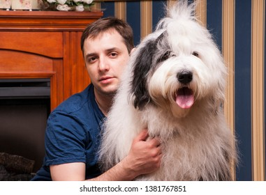 A man with a dog, a large breed, Bobtail. With the dog by the fire. Close up.