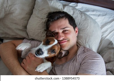 Man with dog lying down in the bed in a morning and looking in to a camera
