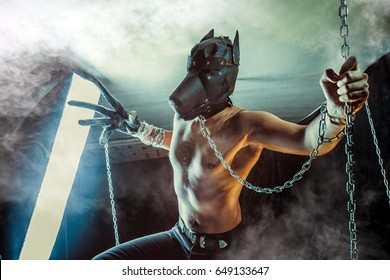 Man in the dog mask on the chain. Dark background.