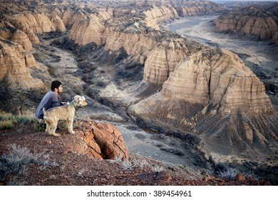 Man and dog on the edge of Zhabyr Canyon (Yellow canyon) in National park Charyn,  Kazakhstan