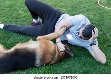 Man and dog playing outside. Friendship contest