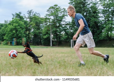 The man with a dog is playing with a soccer ball, Ivano-Frankivsk, Ukraine, June 08, 2018.