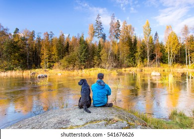 Man and Dog Sitting by River at Autumn
