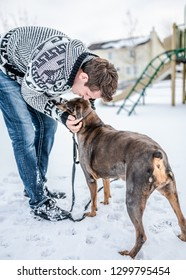 Man and dog in a snow covered neighborhood playground. He bends down to give his furry best friend a kiss.