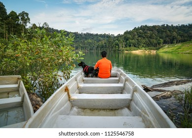 Man and dog spending time beside a lake