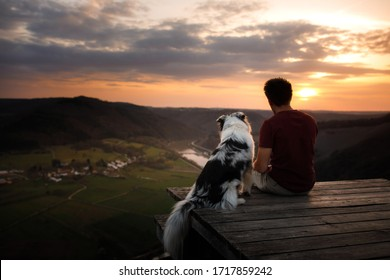 A man with a dog at sunset. walk with a pet. Australian Shepherd and owner in nature