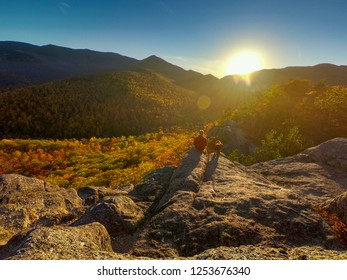 Man and dog watching the sunset with autumn foliage