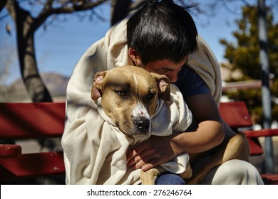 Man with dog wrapped in blanket sitting on bench bent over dog