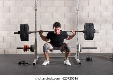 Man doing a back squat exercise raising a barbell weight onto his shoulders while squatting before standing upright