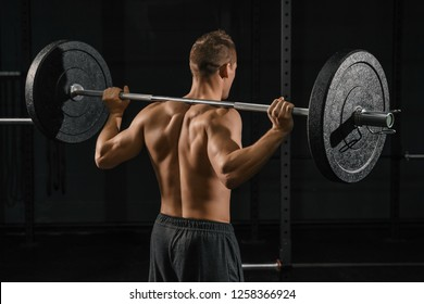 Man doing back squats exercise with a barbell. Cross fit training in a gym.