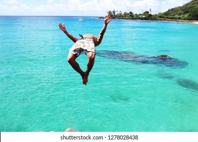 Man doing backflip off cliff into the ocean. Diving cliff ocean. Summer fun lifestyle.
