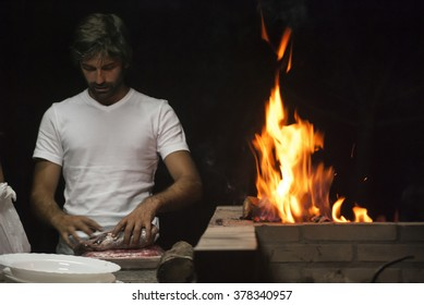 Man doing a barbecue by night. Preparing the meat.