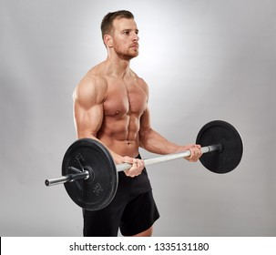 Man doing biceps curl with barbell in studio
