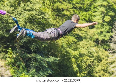 a man doing bungee jumping with a forest in background