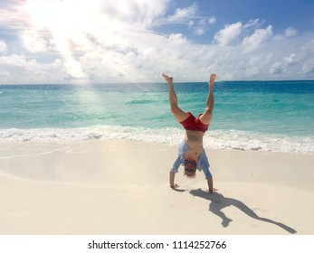 Man doing cartwheel on tropical beach in front of beautiful sea with the sun shining through the clouds