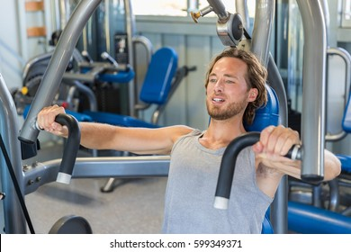 Man doing chest exercises on vertical bench press machine.