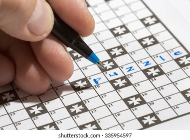 A man is doing crossword puzzle. The man is holding a pencil in his hand and there is a word 'puzzle' already written in the crossword. Crossword puzzles are excellent training for brains.