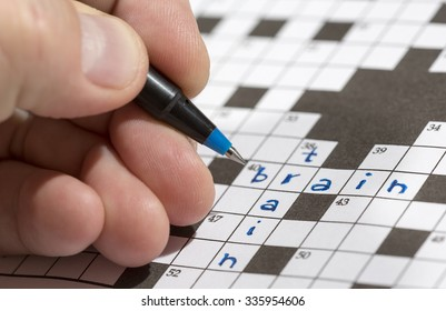 A man is doing crossword puzzle. The man is holding a pencil in his hand and there are words 'train' and 'brain' already written in the crossword. Crossword puzzles are excellent training for brains.