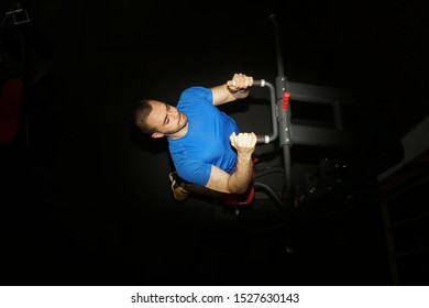 Man doing excersise on a lat machine in gym.Shoulder pull down machine. Fitness man working out lat pulldown training at gym. Upper body strength exercise for the upper back.