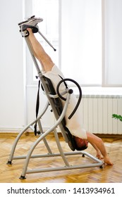 Man doing exercise on inversion table for his back pain