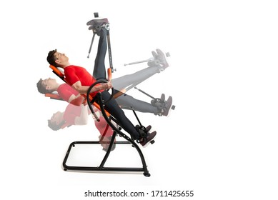Man doing exercise on inversion table for his back pain, isolate