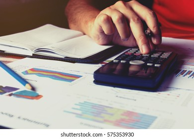Man doing finance and calculate summary report on table.