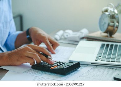 Man doing finances and calculate about cost to real estate investment and in other, tax system.Time for Taxes Money Financial Accounting Taxation Concept