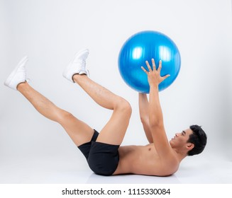 Man doing fitness exercise on pilates ball,Pilates gymnastics is a Germanic evolution of yoga,Used by athletes to improve flexibility and body fitness and by chiropractors for patient recovery.