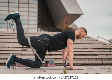 Man doing fitness exercises with elastic resistance band. Handsome young man training with rubber band. Sportsman doing workout outdoors. Healthy lifestyle concept