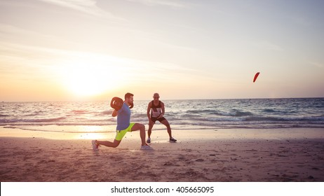 Man doing fitness on the beach with the help of personal trainer. Warm tone, lens flare.