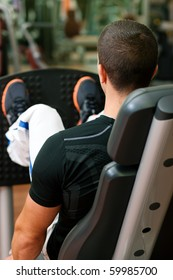 Man doing fitness training on leg press with weights in a gym
