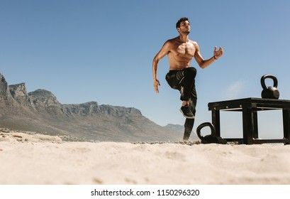 Man doing fitness workout at a beach on a sunny day. Bare chested athletic man exercising on beach with kettlebells on the sand.
