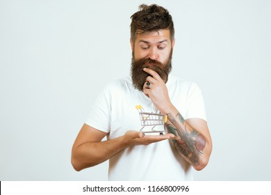 Man doing grocery shopping at supermarket, he is thinking and searching products on the store shelf. Pensive man holding shopping cart. Funny bearded man. Does t know what he wants to buy. Advertising