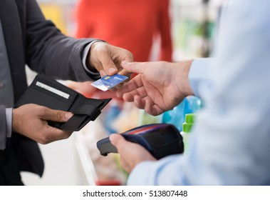 Man doing grocery shopping at the supermarket and paying with a credit card at the store checkout
