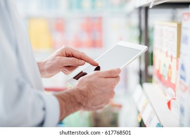 Man doing grocery shopping at the supermarket and using a digital touch screen tablet, he is searching offers and products