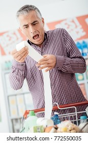 Man doing grocery shopping at the supermarket and checking a long expensive receipt, he is shocked and gasping