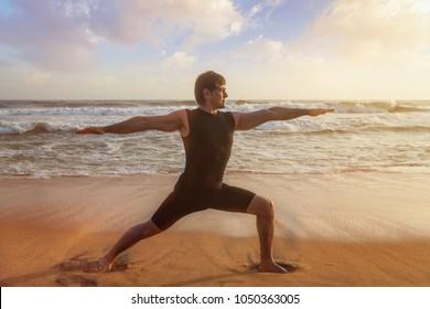 Man doing Hatha yoga virabhadrasana outdoors on ocean beach on sunset. Kerala, India