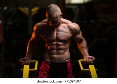 Man Doing Heavy Weight Exercise For Trapezius On Machine