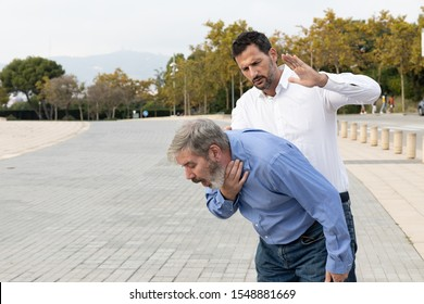 Man doing the Heimlich maneuver to an old man with suffocation due to obstruction of the airway with food