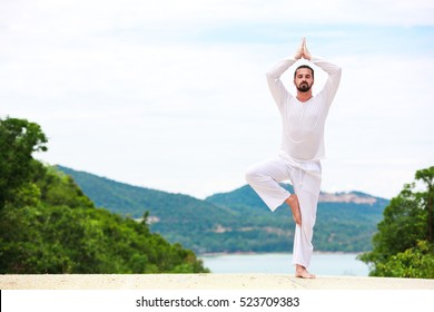 Man Doing Indian classic Yoga at the Sea and Mountains