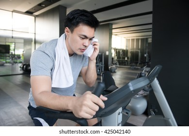 A man doing indoor biking in a fitness club