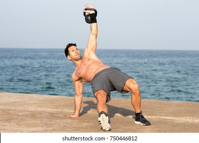 man doing kettlebell exercise by the seaside balancing on one hand
