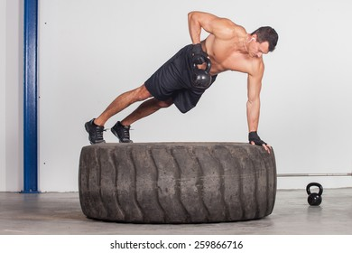 man doing kettlebell training on a tire crossfit