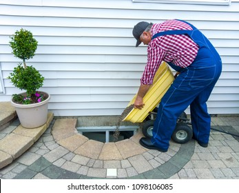 Man doing maintenance on a basement egress window at the side of his house emptying a wheelbarrow full of new pebbles into the cavity surrounded by neat paving