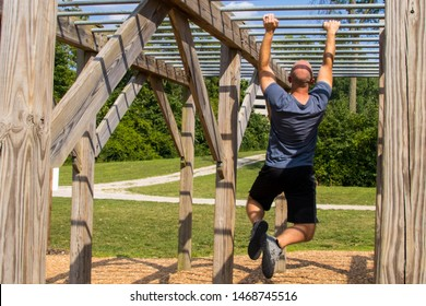 Man doing monkey bars on an obstacle course outside.