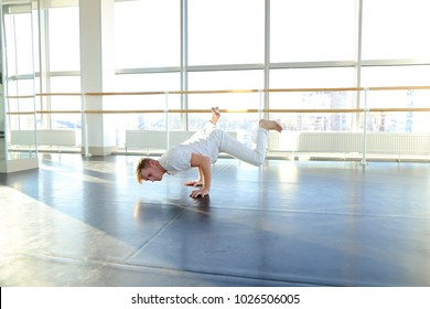 Man doing one arm handstand with legs spread out near window. Boy in white suit training near window. Concept of being in good shape and feat of strength, agility and balance.