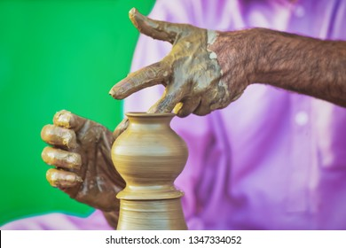 Man doing pottery with rotating wet clay. Two wet hands making art with colorful background.