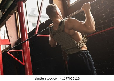 Man doing pull up exercise. Sportsman during his workout in the gym.