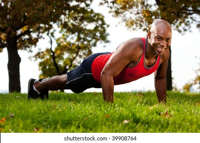 A man doing a push up in a park