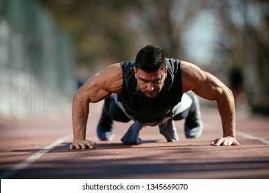 Man doing a push up. Trainer exercises outdoors.